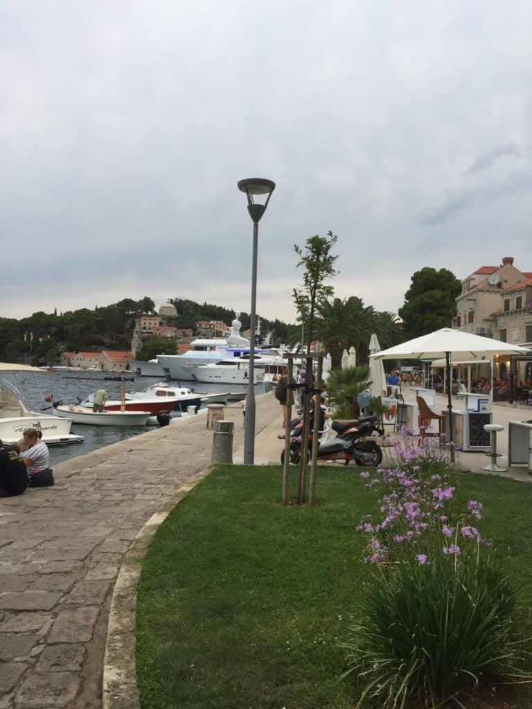 Smuk havnepromenade med restauranter og turbåde